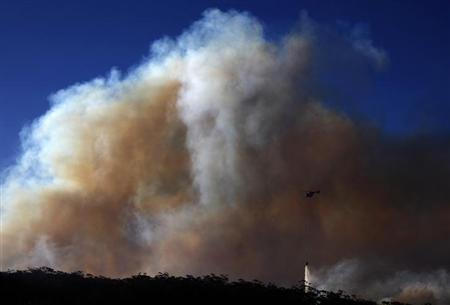 A helicopter drops water on a bushfire approaching homes near the Blue Mountains suburb of Blackheath, located around 70 km (43 miles) west of Sydney, October 23, 2013. REUTERS/David Gray