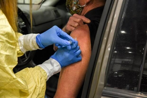 A 64-year-old receives a dose of AstraZeneca-Oxford's COVID-19 vaccine on Monday at Regina's mass drive-thru clinic.  (Saskatchewan Health Authority  - image credit)