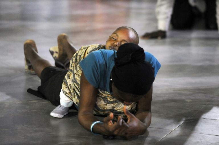 A woman prays with her baby on her back at a past crossover service at Lagos' Redemption Camp, a Nigerian Pentecostal church