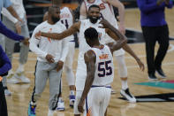 Phoenix Suns guard E'Twaun Moore (55) celebrates with teammates after his winning score against the San Antonio Spurs during the second half of an NBA basketball game against the San Antonio Spurs in San Antonio, Sunday, May 16, 2021. (AP Photo/Eric Gay)