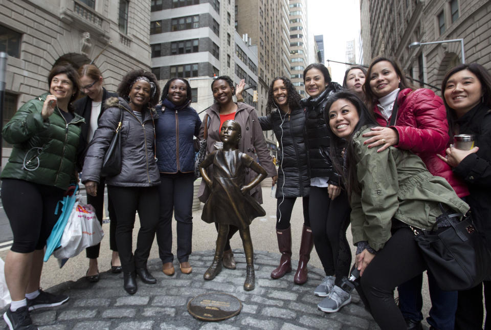 """A group of women stop to pose with a statue of a fearless girl, Wednesday, March 8, 2017, in New York. The statue was installed by an investment firm in honor of International Women's Day. An inscription at the base reads, """"Know the power of women in leadership. She makes a difference. State Street Global Advisors."""" (AP Photo/Mark Lennihan)"""