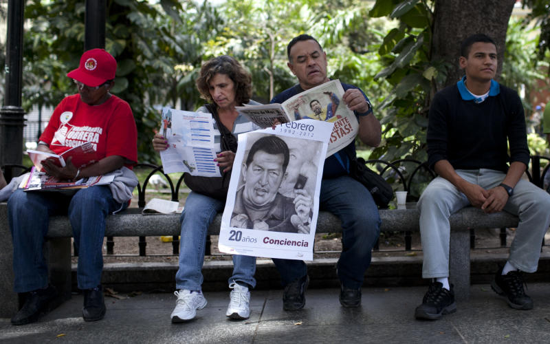 A man holds a poster of Venezuela's President Hugo Chavez as he reads a paper in Bolivar Square in Caracas, Venezuela, Tuesday Feb. 28, 2012. Doctors successfully extracted a tumor from Chavez's pelvic region and he was stable and recovering Tuesday with family at his side, his vice president announced. (AP Photo/Ariana Cubillos)