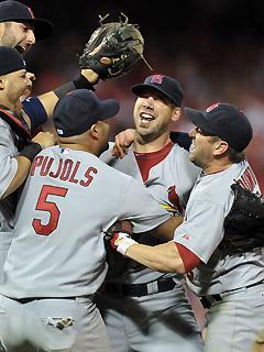 Cardinals pitcher Chris Carpenter is surrounded by teammates after his complete game win clinched the NLDS for St. Louis