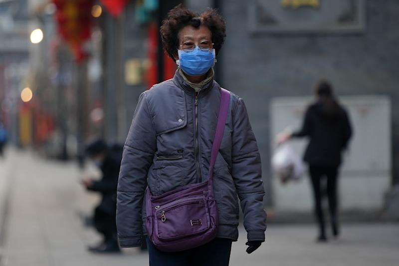 BEIJING, CHINA - FEBRUARY 25: A Chinese woman wears a protective mask on commercial street on February 25, 2020 in Beijing, China. Sunday marked one month since Wuhan was put under lockdown to stop the spread of the deadly new coronavirus, COVID-19. Much of China's capital remains shuttered Monday in an attempt to stop the spread of the pneumonia-like disease that has killed 2,592 and sickened 77,150 in mainland China, mostly in Hubei province. (Photo by Lintao Zhang/Getty Images)