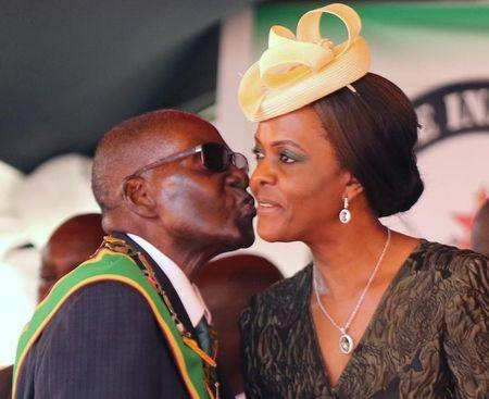 Zimbabwean President Robert Mugabe kisses his wife Grace at a rally to mark the country's 37th independence anniversary in Harare