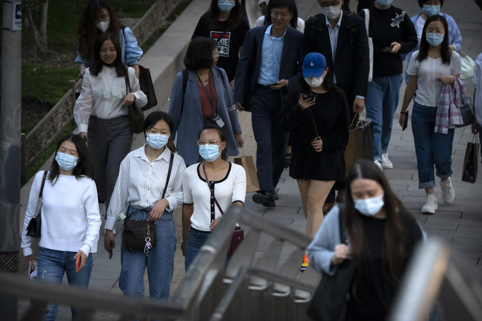 People wearing face masks to protect against COVID-19 walk along a street in the central business district in Beijing, Thursday, Sept. 16, 2021. China on Thursday reported several dozen additional locally-transmitted cases of coronavirus as it works to contain an outbreak in the eastern province of Fujian. (AP Photo/Mark Schiefelbein)