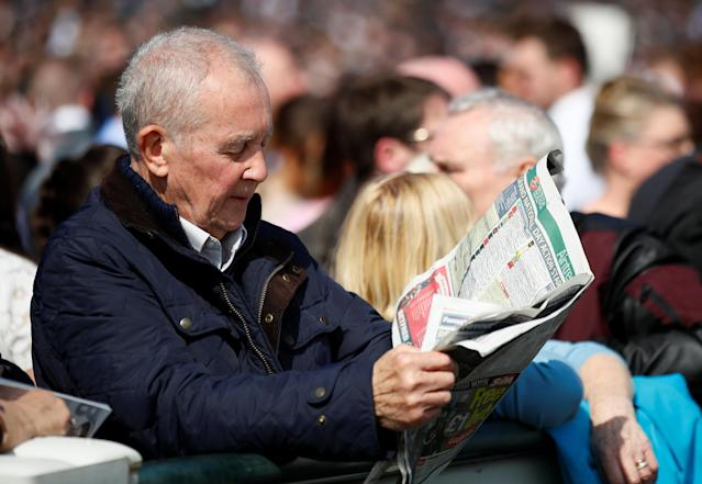 Horse Racing - Grand National Festival - Aintree Racecourse, Liverpool, Britain - April 14, 2018 Racegoer reads a newspaper during the Grand National Festival Action Images via Reuters/Jason Cairnduff