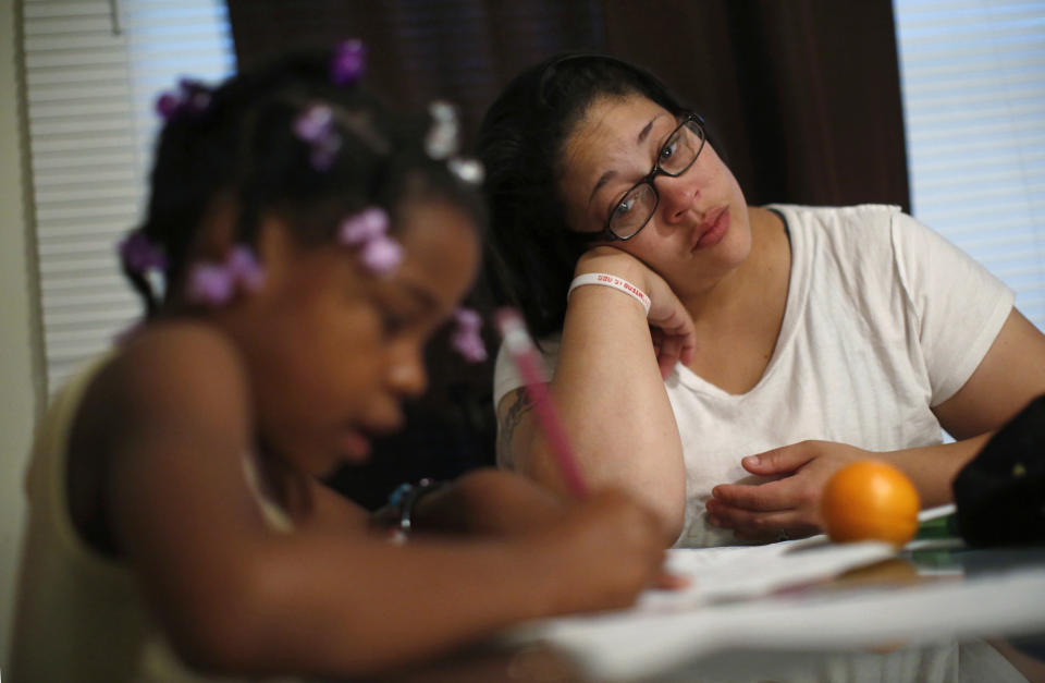 Delores Leonard (R) helps her daughter Erin with her homework at the breakfast table before heading to work at a McDonald's Restaurant in Chicago, Illinois, September 25, 2014. Leonard, a single mother raising two daughters, has been working at McDonald's for seven years and has never made more than minimum wage.  Picture taken September 25, 2014.   REUTERS/Jim Young (UNITED STATES - Tags: BUSINESS EMPLOYMENT TPX IMAGES OF THE DAY)