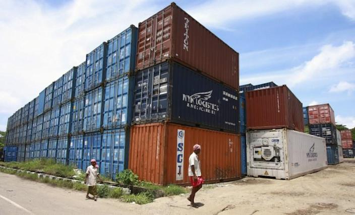 Workers walk past containers at a depot on Willingdon Island