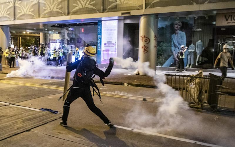 A demonstrator throws back a tear gas canister towards riot police on July 28 - Bloomberg