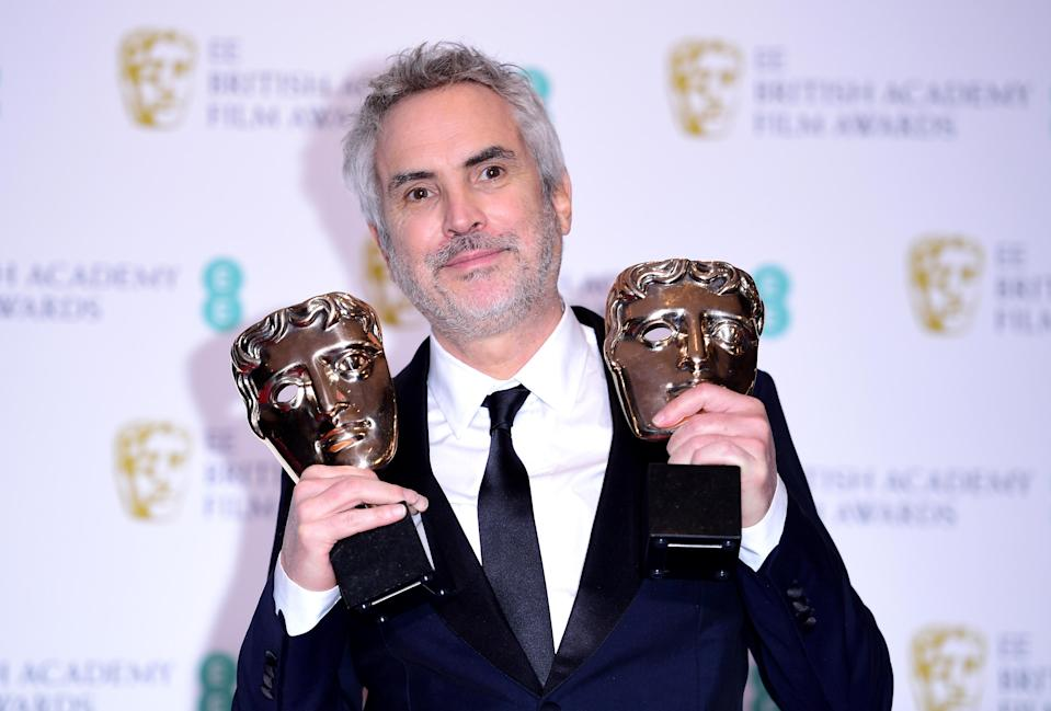 Alfonso Cuaron holds aloft two of his BAFTAs for <i>Roma</i> (PA)
