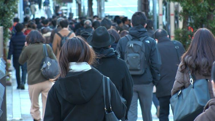 Japanese commuters photographed from behind, including several women.