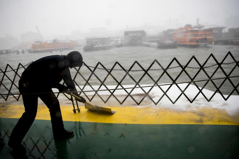 A member of the Staten Island ferry crew clears the deck as the ferry approaches the terminal during a snowstorm, Tuesday, March 14, 2017, in New York. (AP Photo/Mary Altaffer)