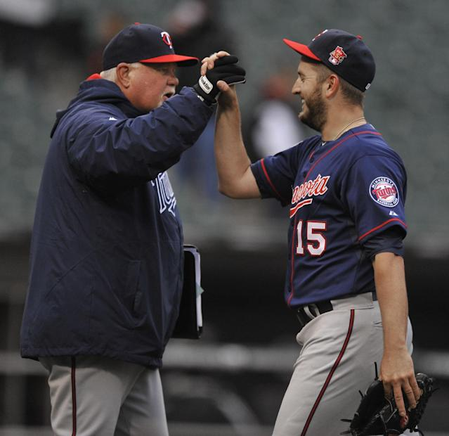 Minnesota Twins manager Ron Gardenhire, left, celebrates with closing pitcher Glen Perkins (15) after they defeated the Chicago White Sox 10-9 in a baseball game in Chicago, Thursday, April 3, 2014. (AP Photo/Paul Beaty)