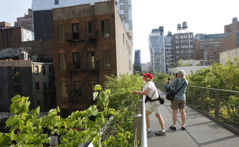 FILE - In this June 7, 2011, file photo, visitors pause to take in views of the city's West Side on the High Line, an industrial elevated railway converted into a city park, in New York. Many plant and landscape experts have begun thinking of plants in terms of communities, instead of as individual specimens. They recommend that home gardeners look to the wild for inspiration. The idea is to think of plants as interrelated species. That shift in thinking got underway in earnest with the opening of the High Line. In a move considered radical at the time _ but replicated in parks and gardens across the country since then _ the designers of the High Line went with a wilder look, with plantings resembling roadside grasses and wildflowers more than a traditional garden. (AP Photo/Kathy Willens, File)