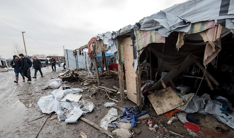 "People walk in the southern part of the so-called ""Jungle"" migrant camp in Calais, northern France, which is being dismantled, on March 10, 2016 (AFP Photo/Denis Charlet)"