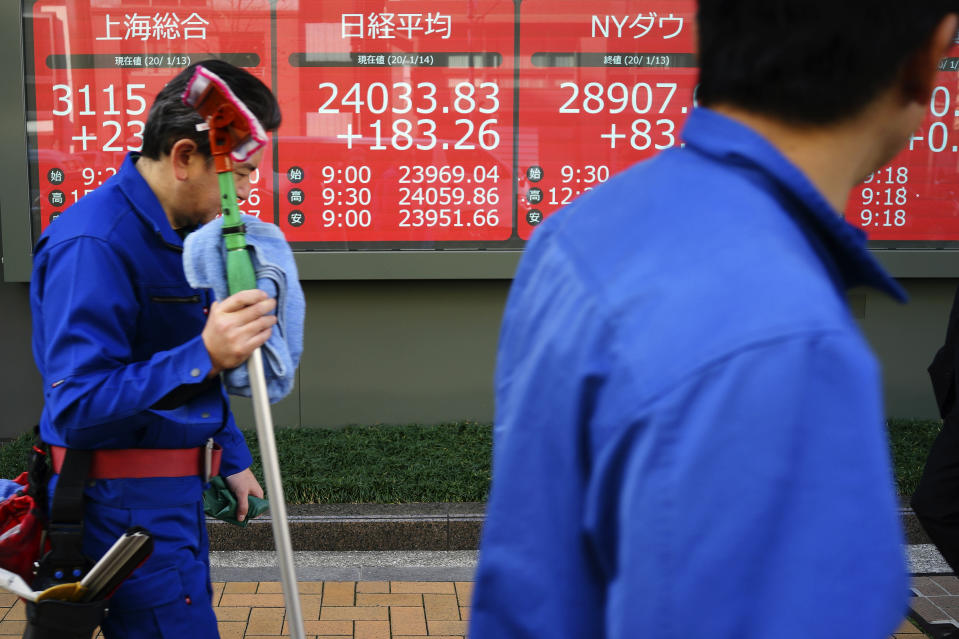 Workers walk past an electronic stock board showing Japan's Nikkei 225 index at a securities firm in Tokyo Tuesday, Jan. 14, 2020. Asian shares followed Wall Street higher on Tuesday amid optimism that a trade deal between the U.S. and China will be a boon for the regional economy. (AP Photo/Eugene Hoshiko)
