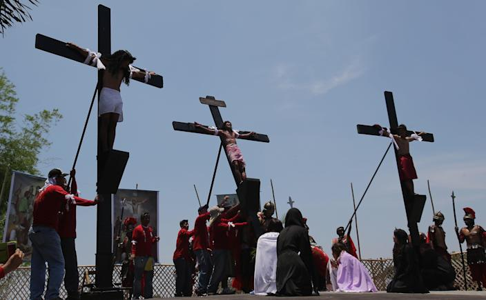 A Filipino devotee who was nailed to a cross is lifted as they try to re-enact the crucifixion of Jesus Christ in San Juan village, Pampanga province, northern Philippines on Friday, April 18, 2014. Church leaders and health officials have spoken against the practice which mixes Roman Catholic devotion with folk belief, but the annual rites continue to draw participants and huge crowds. (AP Photo/Aaron Favila)