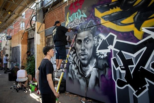 Men work on a mural of Jamal Francique in Toronto's Graffiti Alley.