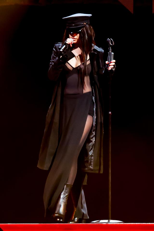 <p>Before the beat picked up and backup dancers stripped off her outer layers, Selena Gomez covered up her sheer dress with high slits, cutouts, and visible granny panties with a black silk trench and a hat possibly stolen from a policeman guarding her locker room door.<i>Photo: Getty Images</i></p>