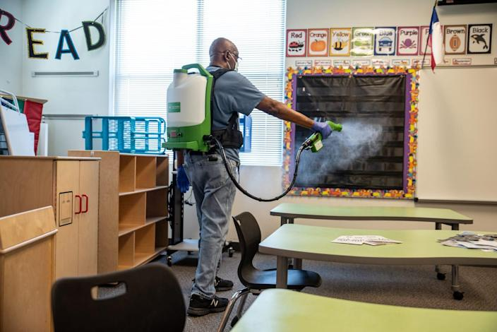 A custodian cleans a classroom at Akin Elementary in Leander, Texas on Thursday. The school has been preparing for possible return of students by cleaning and disinfecting classrooms to help prevent the spread of coronavirus.