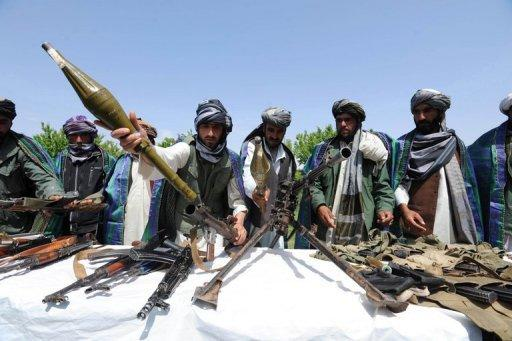 Former Taliban fighters display their weapons as they join Afghan government forces during a ceremony in Herat province on April 26. The US, Pakistan and Afghanistan have agreed to set up a group to look at how Taliban fighters who wanted to be part of the peace process could be included