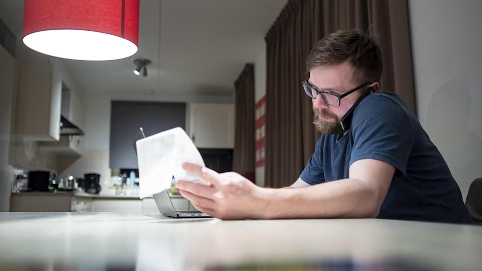 Calm, focused bearded man with glasses manages finances by phone while sitting at home in the kitchen, he looks at the receipt he holds in his hand, next to him is an open laptop.