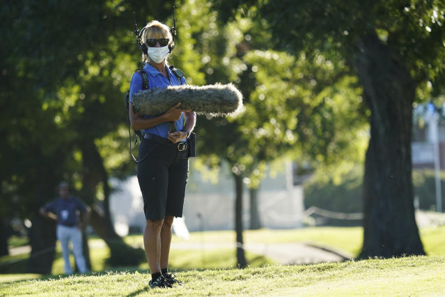 A sound technician wears a protective mask during the first round of the Charles Schwab Challenge golf tournament at the Colonial Country Club in Fort Worth, Texas, Thursday, June 11, 2020. (AP Photo/David J. Phillip)