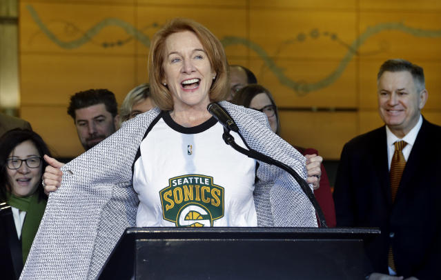 Seattle mayor Jenny Durkan pulls back her jacket to reveal a Seattle SuperSonics T-shirt as Tim Leiweke (right), the CEO of Los Angeles-based Oak View Group, looks on. (AP)