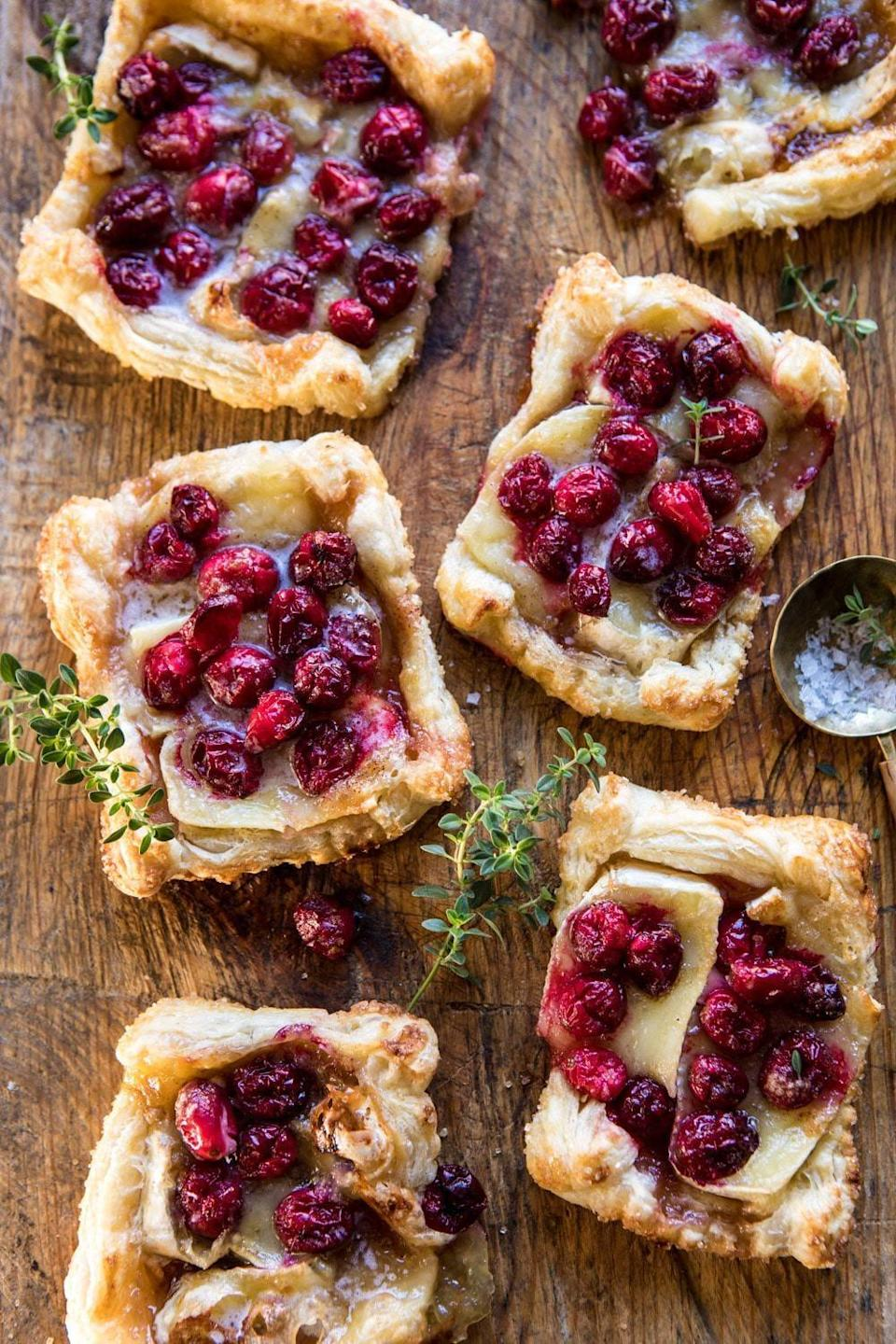 "<p>Quick, easy, and a fan favorite, these tarts are too good to be true. Creamy brie, tangy cranberries, and a fluffy puff pastry work together to make these cheese-filled tarts ready to be served in no time. Since this recipe is made to make 12 servings, you can either freeze them for later, give a couple to your family, or warm them up for days to come.</p> <p><strong>Get the recipe</strong>: <a href=""https://www.halfbakedharvest.com/cranberry-brie-pastry-tarts/"" class=""link rapid-noclick-resp"" rel=""nofollow noopener"" target=""_blank"" data-ylk=""slk:cranberry brie pastry tarts"">cranberry brie pastry tarts</a></p>"
