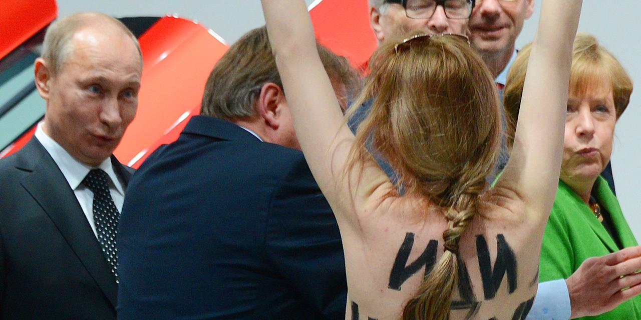 A topless demonstrator with written messages on her back walks towards Russian President Vladimir Putin , left and German Chancellor Angela Merkel, right, during the opening tour at the Hannover Fair in Hannover, Germany, Monday April 8, 2013. Several activists stormed the booth of Volkswagen to demonstrate in presence of the politicians. (AP Photo/dpa,Jochen Lurbke)
