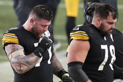 Pittsburgh Steelers offensive guard Matt Feiler (71) and offensive tackle Alejandro Villanueva (78) walk off the field after the Cleveland Browns intercepted a pass by quarterback Ben Roethlisberger during the fourth quarter of an NFL wild-card playoff football game, late Sunday, Jan. 10, 2021, in Pittsburgh. (AP Photo/Keith Srakocic)