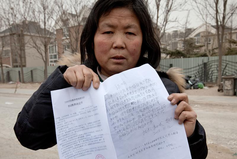 In this Saturday, March 9, 2013 photo, Zhao Meifu, a farmer from Gansu province shows the papers of her labor camp detention in Beijing. Zhao had been seeking redress for decades over a land grab by village officials. Tired of her complaints, police saw the labor camp as a quick way to get rid of her. She was locked up in a long hated and often abused penal system known as labor re-education. Chinese police have used it to lock up tens of thousands of people for up to four years without a trial or a judge's review. Established to punish early critics of the Communist Party, it was retooled to focus on petty criminals but now is used by local officials to deal with people challenging their authority on issues including land rights and corruption. (AP Photo/Andy Wong)