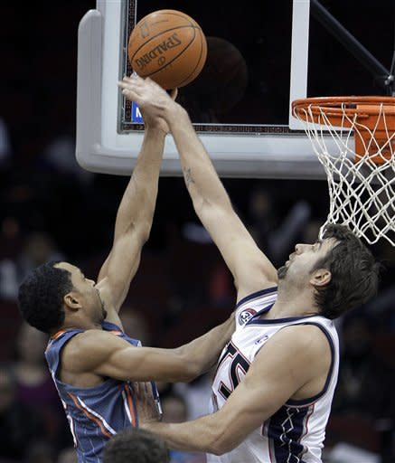 New Jersey Nets' Mehmet Okur, right, of Turkey, makes a block attempt on a shot by Charlotte Bobcats' Gerald Henderson during the second quarter of an NBA basketball game, Sunday, Jan. 22, 2012, in Newark, N.J. (AP Photo/Julio Cortez)