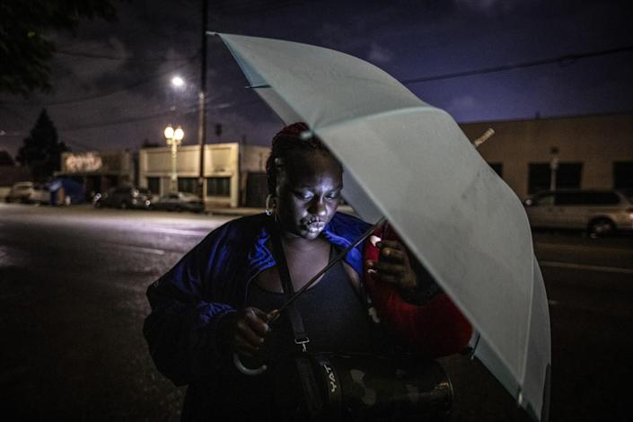 A woman holds an umbrella as a cell phone illuminates her face