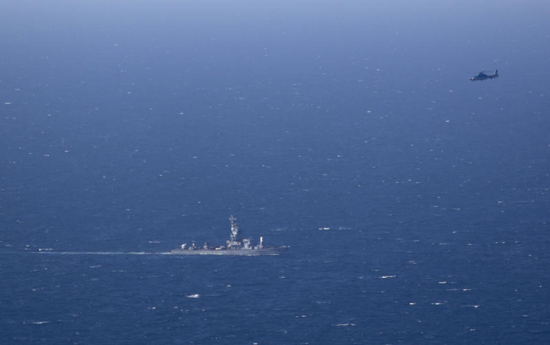 An Israeli military naval ship and an Israeli air force helicopter operate off the coast of Haifa, northern Israel, Thursday, April 25, 2013. Israel shot down a drone Thursday as it approached the country's northern coast, the military said. Suspicion immediately fell on the Hezbollah militant group in Lebanon. The incident was likely to raise already heightened tensions between Israel and Hezbollah, a bitter enemy that battled Israel to a stalemate during a monthlong war in 2006. (AP Photo/Ariel Schalit)