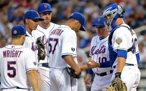 New York Mets' Johan Santana, center, gives the ball to manager Terry Collins, second from right, after being taken out of the baseball game against the Atlanta Braves in the second inning at Citi Field in New York, Saturday, Aug. 11, 2012. Santana gave up eight hits and eight earned runs in his first start since July 20. (AP Photos/Henny Ray Abrams)
