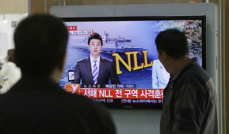 """People watch a television news program reporting about North Korea's plan to conduct live-fire drills, at a Seoul train station in Seoul, South Korea, Monday, March 31, 2014. South Korea said North Korea has announced plans to conduct live-fire drills near the rivals' disputed western sea boundary. Seoul's Defense Ministry said North Korea says it will conduct firing drills in seven areas north of the sea boundary. The letters read """"Western Sea NLL (Northern Limit Line) Firing drills."""" (AP Photo/Lee Jin-man)"""