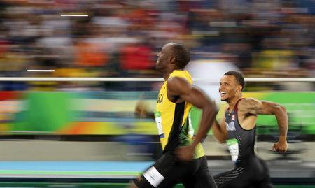 FILE PHOTO: 2016 Rio Olympics - Athletics - Semifinal - Men's 200m Semifinals - Olympic Stadium - Rio de Janeiro, Brazil, August 17, 2016. Usain Bolt (JAM) of Jamaica and Andre De Grasse (CAN) of Canada smile as they compete. REUTERS/Phil Noble/File Photo