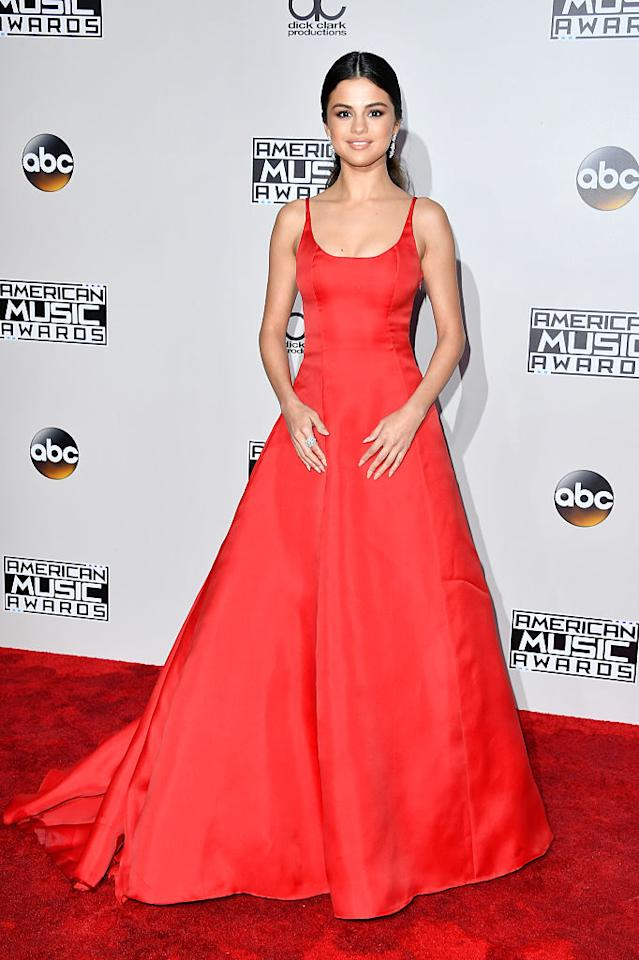 <p>Selena Gomez, making one of her first official public appearances since August, ruled the red carpet in a bright red dress. The silhouette, while simple with spaghetti straps and a billowing skirt, still made quite the impression. The singer accessorized with diamond earrings and a matching cocktail ring and had her hair pulled back in a low ponytail with a center part. <em>(Photo: Getty Images)</em> </p>