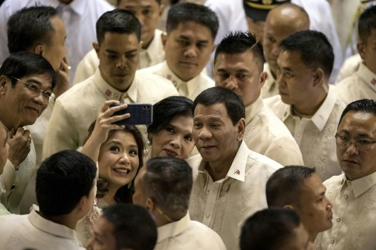 Duterte poses for a selfie while surrounded by supporters and lawmakers after delivering his State of the Nation address