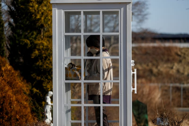 The Wider Image: Japan's tsunami survivors call lost loves on the phone of the wind