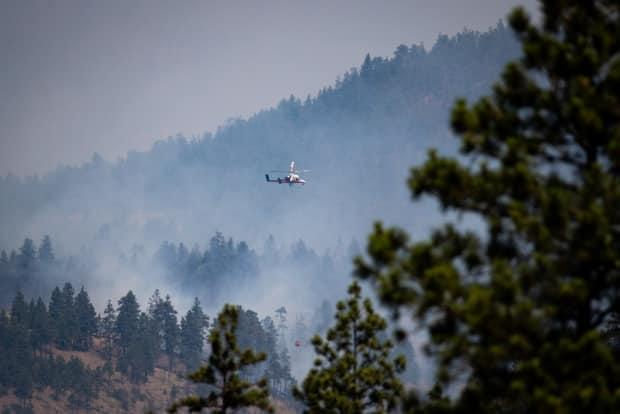 A helicopter pilot prepares to drop water on a wildfire burning in Lytton, B.C., on Friday. (Darryl Dyck/The Canadian Press - image credit)