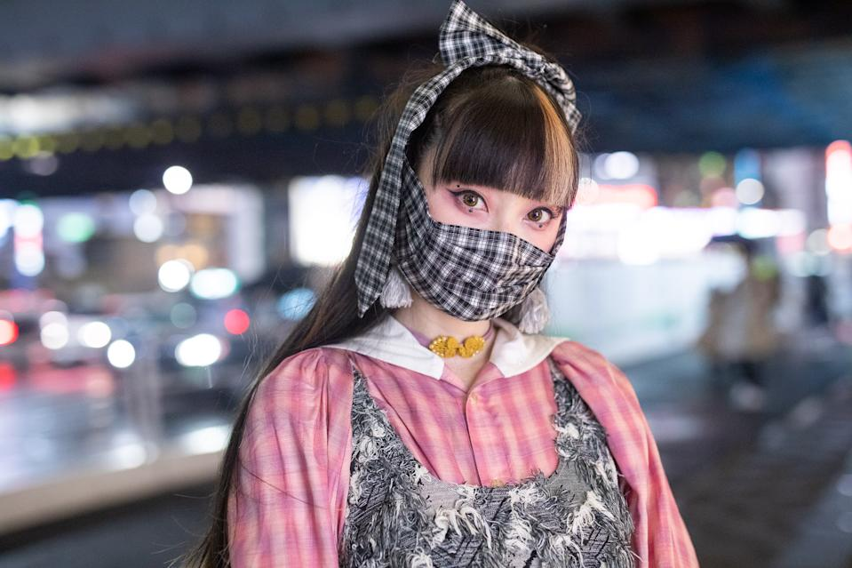 TOKYO, JAPAN - OCTOBER 17: Rinrin is seen on the street wearing Perminute shirt and dress, plaid print face mask and hair tie, yellow leggings and black shoes during the Rakuten Fashion Week Tokyo 2021 Spring/Summer on October 17, 2020 in Tokyo, Japan. (Photo by Matthew Sperzel/Getty Images)