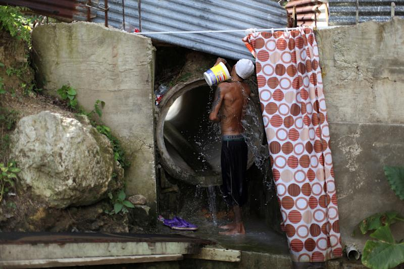 Israel Ayala takes a bath with water coming through a pipe on Oct. 19, 2017, after Puerto Rico was hit by Hurricane Maria in September.