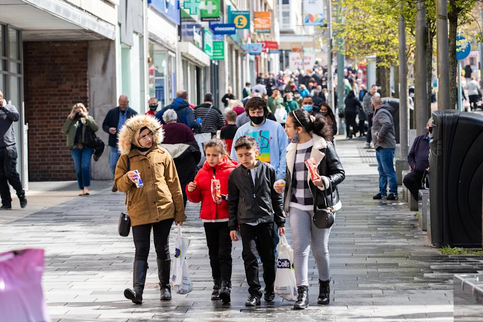 PLYMOUTH, ENGLAND - APRIL 12: Shoppers walking through the City Centre on April 12, 2021 in Plymouth, United Kingdom. England has taken a significant step in easing its lockdown restrictions, with non-essential retail, beauty services, gyms and outdoor entertainment venues among the businesses given the green light to re-open with coronavirus precautions in place. Pubs and restaurants are also allowed to open their outdoor areas, with no requirements for patrons to order food when buying alcoholic drinks. (Photo by William Dax/Getty Images)