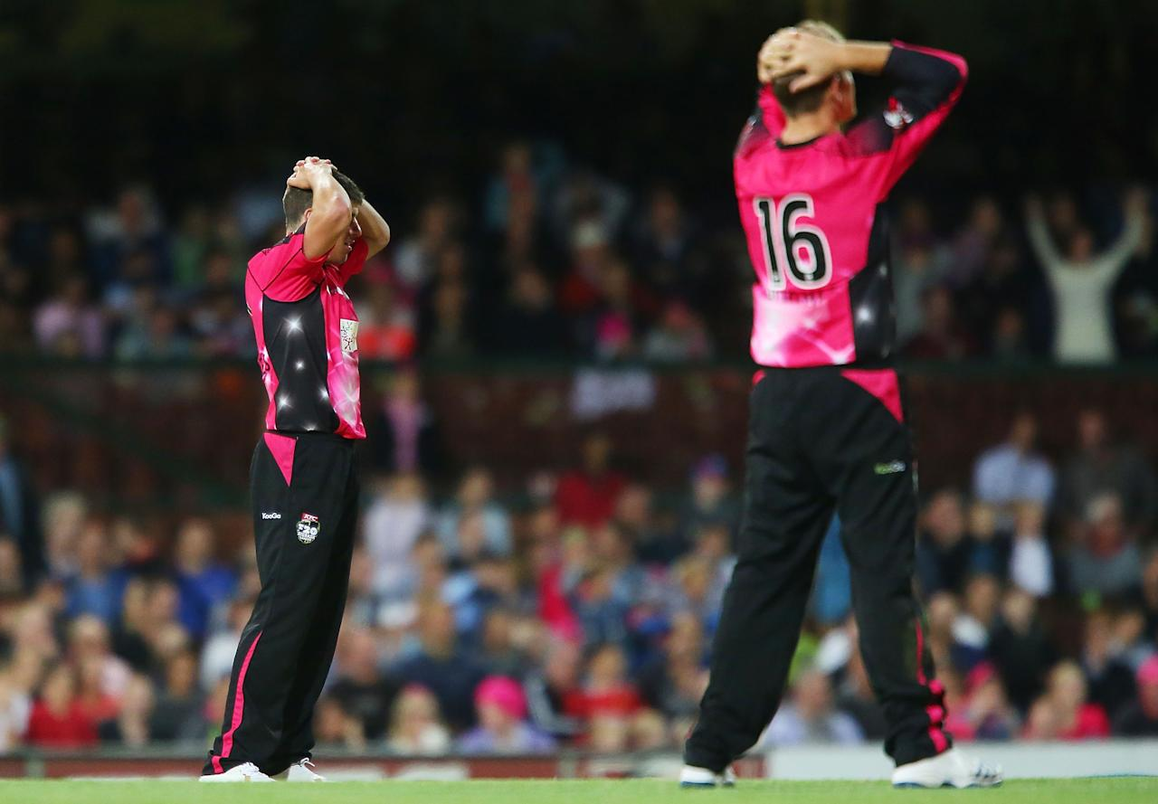 SYDNEY, AUSTRALIA - DECEMBER 26:  Moises Henriques and Daniel Hughes of the Sixers look dejected after losing the match to the Hurricanes during the Big Bash League match between the Sydney Sixers and the Hobart Hurricanes at SCG on December 26, 2012 in Sydney, Australia.  (Photo by Brendon Thorne/Getty Images)