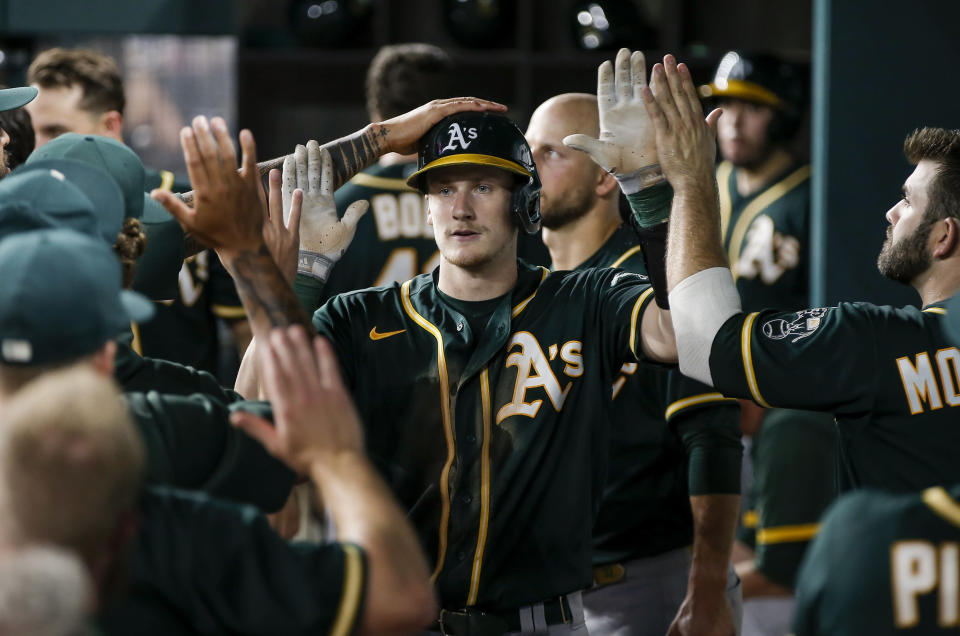 Oakland Athletics' Sean Murphy (12) is congratulated by teammates after hitting a solo home run during the seventh inning of a baseball game against the Texas Rangers, Wednesday, June 23, 2021, in Arlington, Texas. (AP Photo/Brandon Wade)