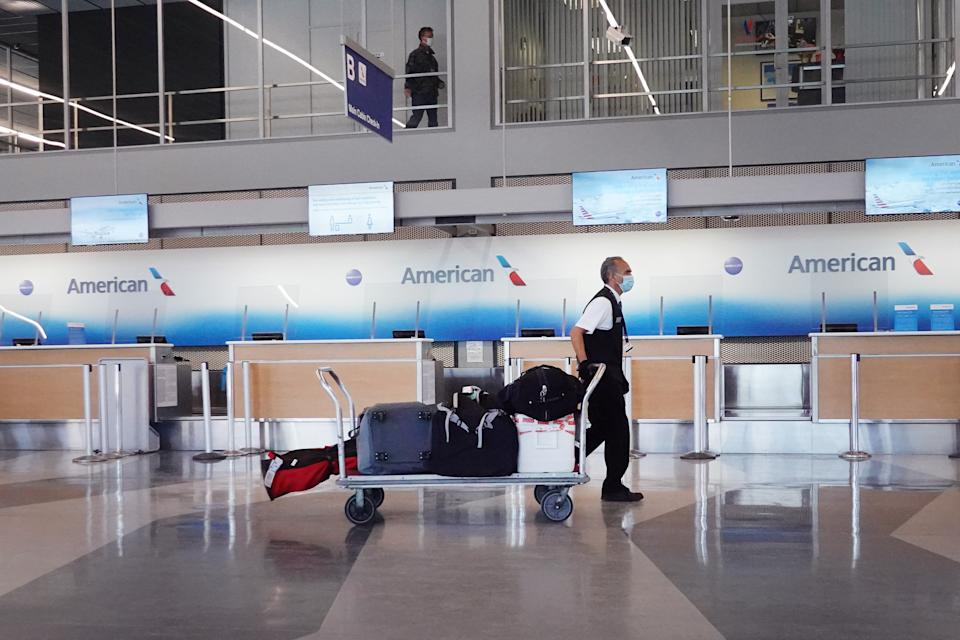 A worker wearing a face mask hauls luggage past an American Airlines counter in an airport