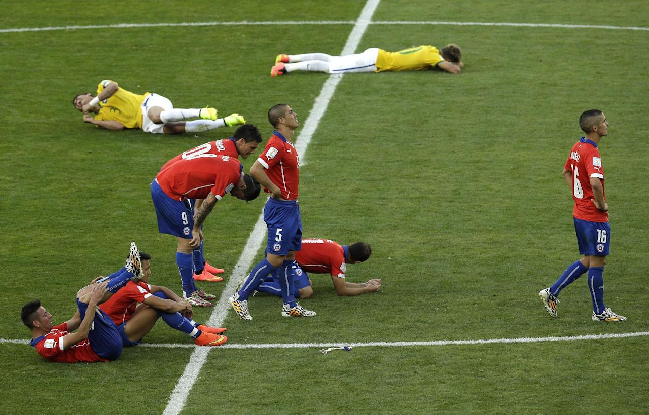 Players of Chile, front, and Brazil react after Chile's Gonzalo Jara missed to score from the penalty spot during the World Cup round of 16 soccer match between Brazil and Chile at the Mineirao Stadium in Belo Horizonte, Brazil, Saturday, June 28, 2014. Brazil won 3-2 on penalties after the match ended 1-1 draw after extra-time. (AP Photo/Hassan Ammar)